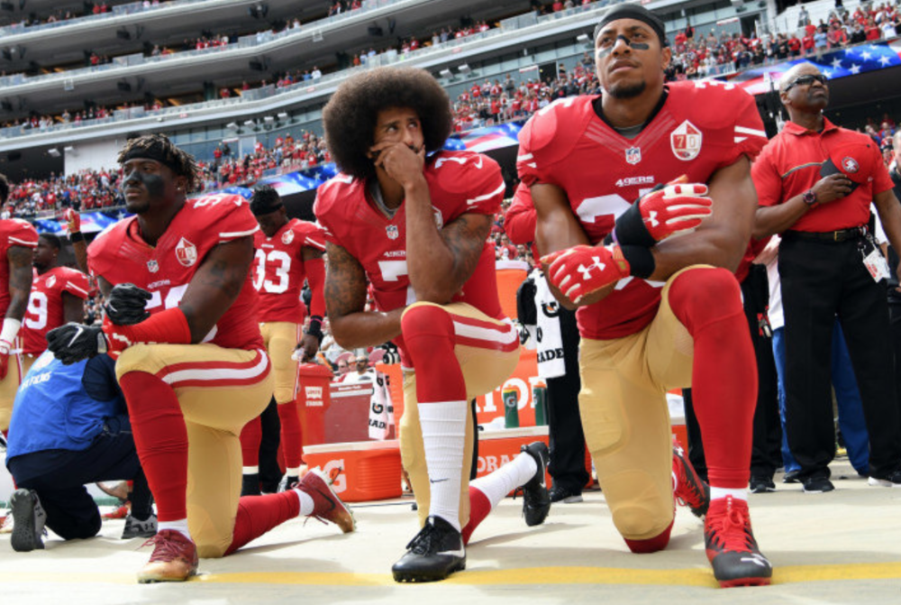Colin Kaepernick takes a knee during the national anthem alongside his teammates during the 2016 NFL season. Kaepernick began his protest during the preseason in protest of police brutality and racial injustices against African Americans. (Flickr)