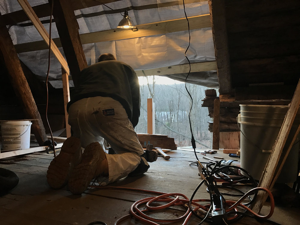 Roofer Bob Zoni gathers his tools underneath a tarp where the house's roof once was.