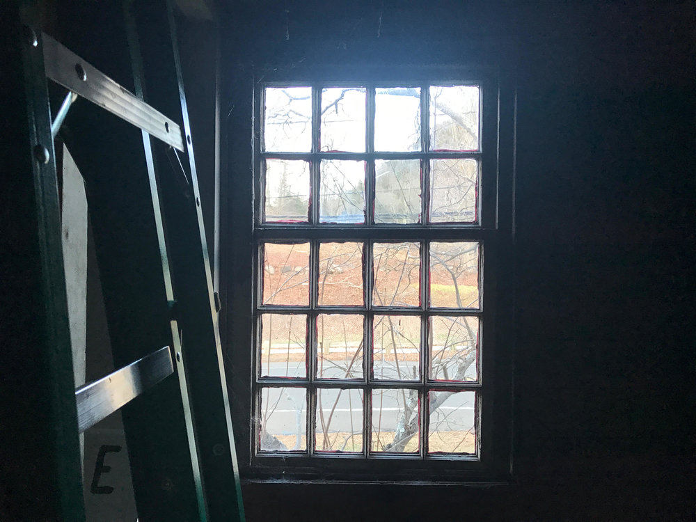 A ladder leans on a wall beside an upstairs hallway window that peeks out unto Mount Carmel Ave. Zoni's ladder and other work tools take up some of the space upstairs during construction.