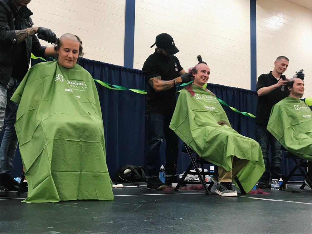 Three shavees lose their locks at Monday night's event.