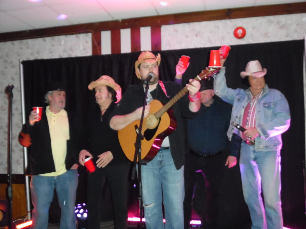 """Three ETAs, Ed Butski, Gordie McNeil, and Doug McKenzie, join Kenny Rogers (Ron Provo) and Toby Keith (Brian McKenzie) on stage for their rendition of Toby Keith's song """"Red Solo Cup""""."""