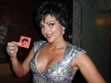Amberley Beatty, Pasty Cline Tribute Artist, models holding a SIDEBURNS Magazine business card.
