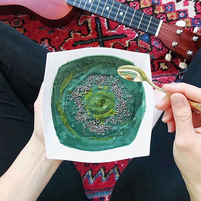 It's a strumming and spirulina smoothie bowl kind of Sunday to keep cool out of the 95°F heat. I just made a variation of @melissawoodhealth's ultimate beauty boosting and energizing spirulina smoothie and it has literally turned my day around! I was feeling slightly sick and sluggish earlier but after having this deliciousness I feel 1,000% better! I hadn't tried this until today and now I am hooked. 💖 • I recently found Melissa after listening to an amazing episode of @julssolomon's #TheInfluencerPodcast (by the way, everyone should listen it is THE most helpful, informative podcast I think I've ever listened to!). I enjoyed hearing her so much that I now love to follow along on IG and her website. 😍 • I didn't have all the ingredients, but luckily the main ones and I added a few extra! Here's what I put in- 1 C. raw coconut water 1 frozen banana  1 C. riced frozen cauliflower 1 C. blueberries 1/2 avocado 1/2 peeled cucumber  Blend all ingredients until smooth, then I added 1 Tbsp spirulina so the powder didn't fly everywhere in initial mix & I also add 3-4 drops of stevia for extra sweetness.  Top with sprinkle of chia seeds and turmeric for extra nutrients and a fun design!  Check out the original recipe on her website and follow these women for some serious #motivation before the week ahead! 💫 . . —  #livecolorfully #colorpop #prettyfood #foodstyling #f52grams #feedfeed #homemade #healthyeats #nourish #flashesofdelight #abmlifeiscorful #foodie #foodblogger #ncblogger  #foodgawker #eeeeeats #foodart #foodiegram #healthyeating #spoonfeed #buzzfeast #cheersyears