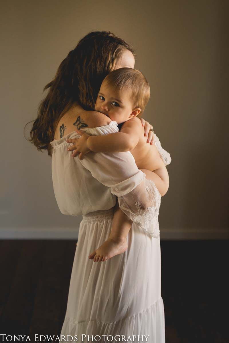 Tonya Edwards | Oroville Photographer | mother in a white dress holding her bare baby looking over her shoulder