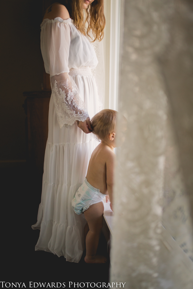 Tonya Edwards | Oroville Photographer | mother and baby looking out the window mother touching baby hair on back of head