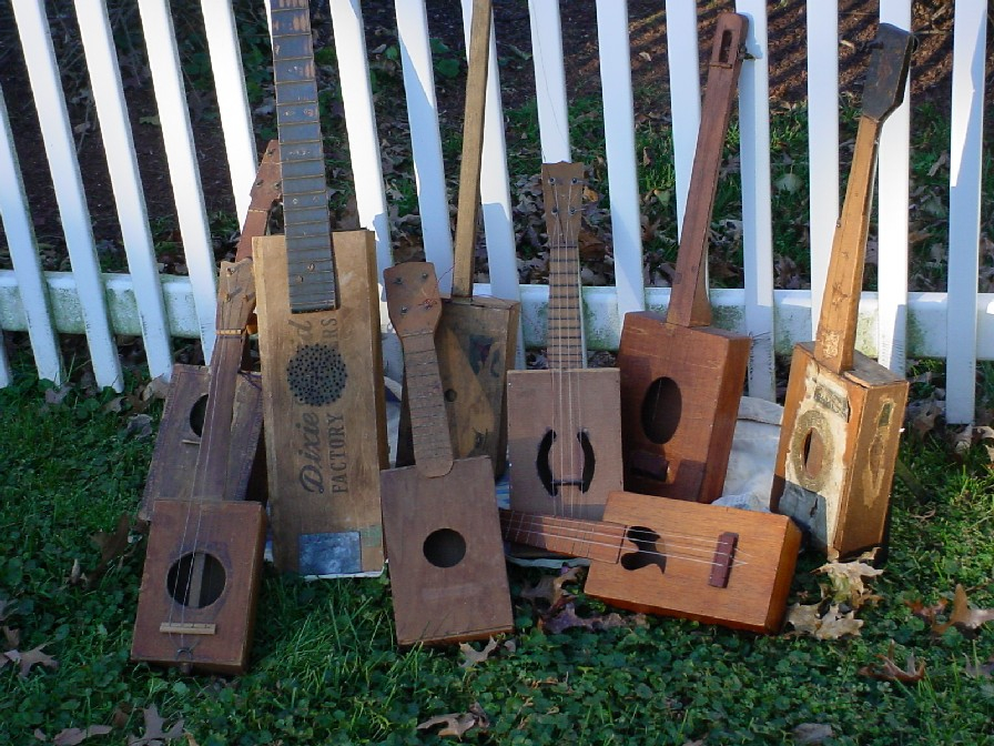 A collection of antique cigar box guitars, banjos and ukuleles. From the National Cigar Box Guitar Museum. Photo by Shane Speal.  Cigarboxguitar (talk) (Uploads) [Public domain] via Wikimedia Commons