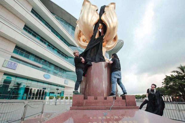 Joshua Wong werd enkele dagen geleden gearresteerd na een actie waarbij een zwart doek over een standbeeld van de Bauhinia - symbool voor Hongkong - werd geworpen. © Demosisto