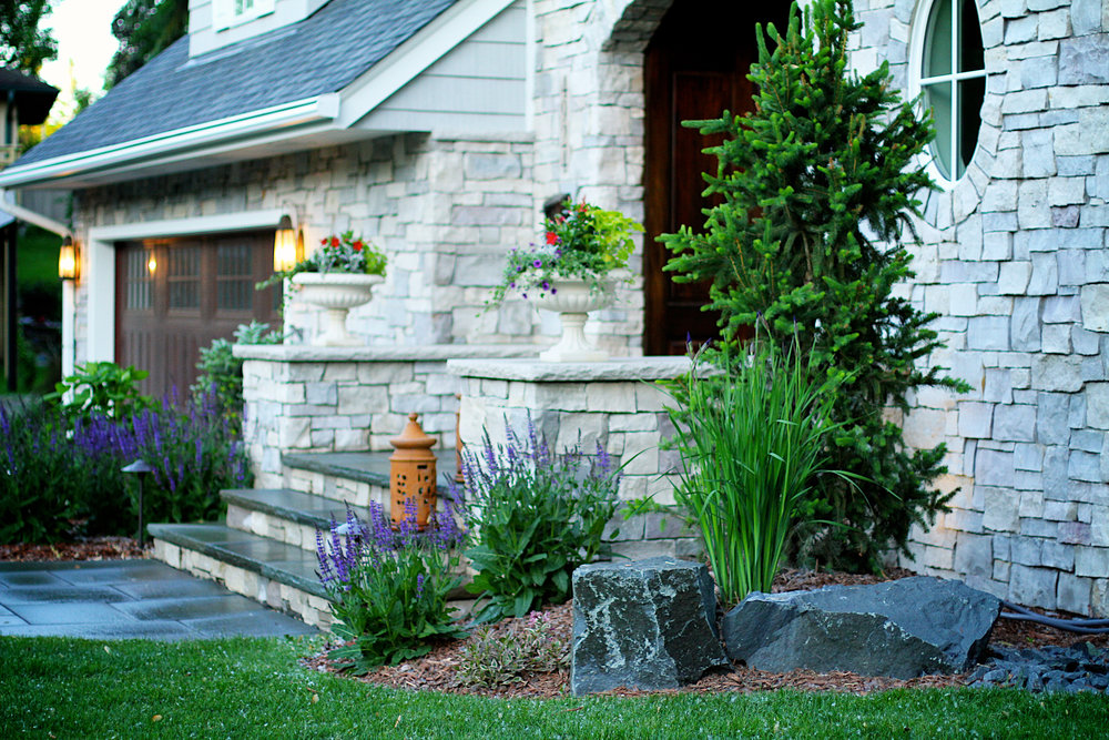 Edina curb appeal goes from drab to fab. after an internal renovation, new landscape was added to equal the beauty. natural stones and plants were chosen to complete the look.