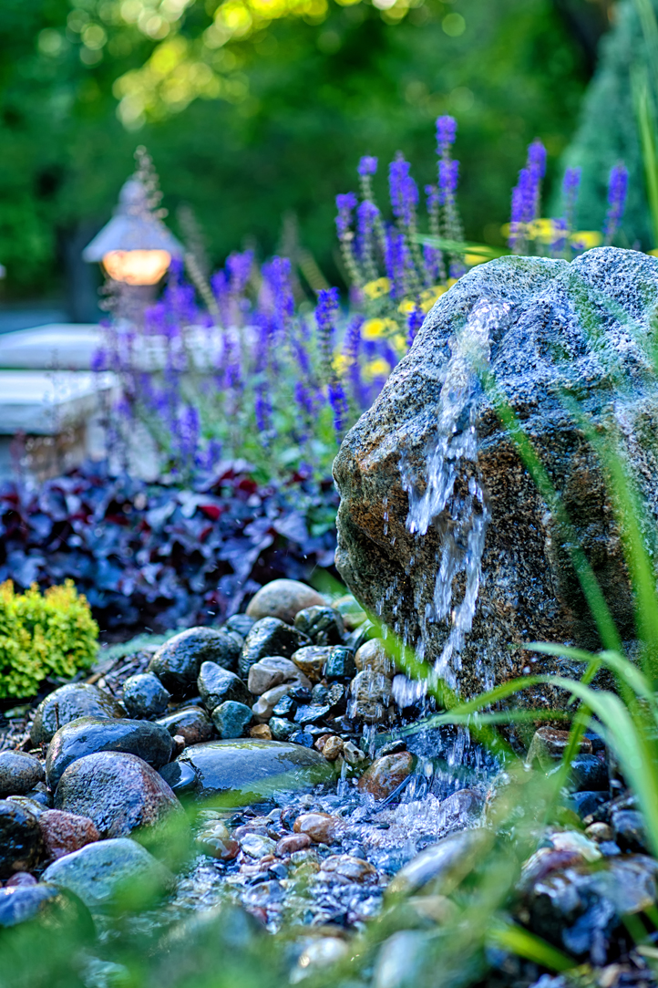 Close up of Edina waterfall tucked within the beautiful backyard landscape.