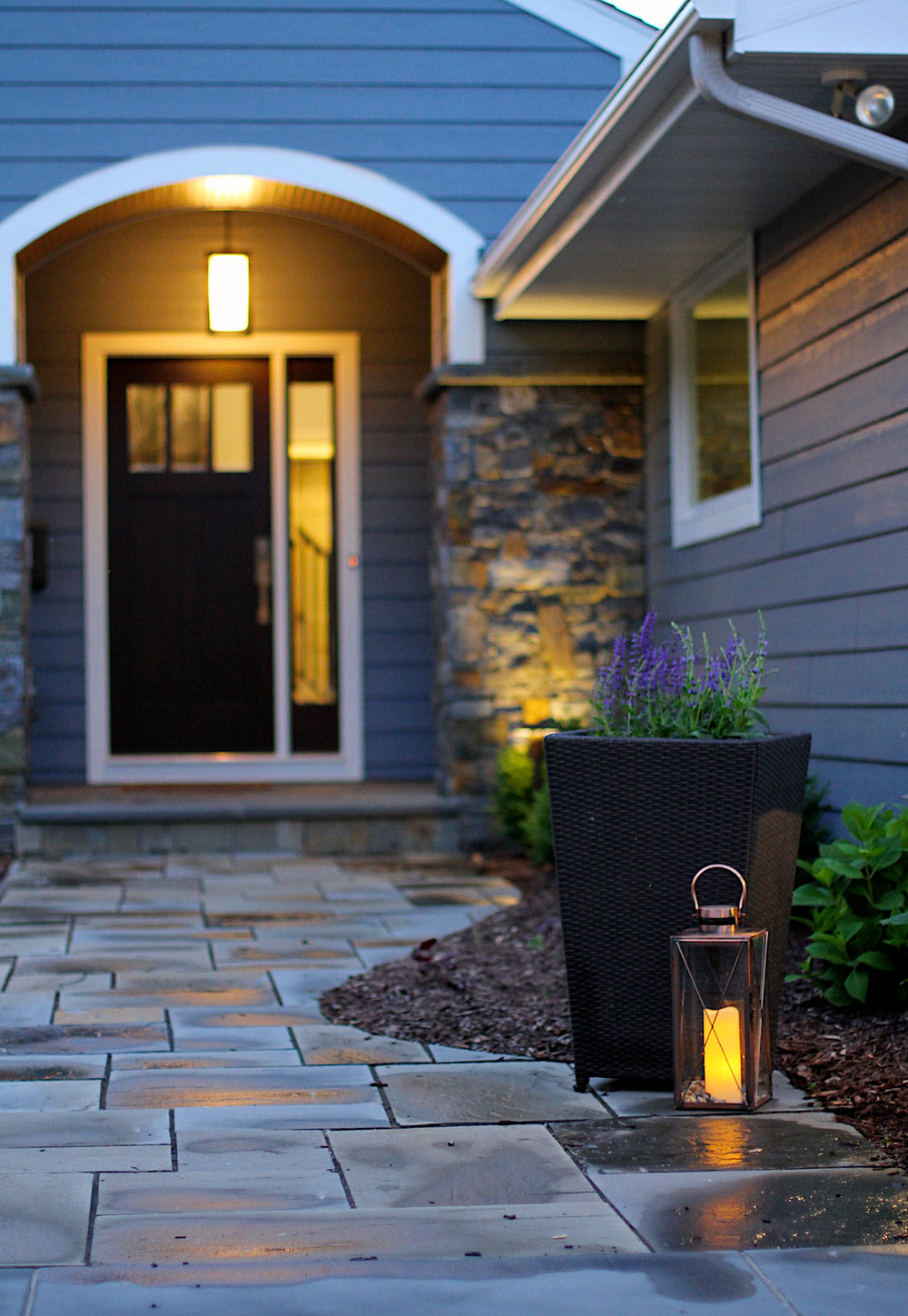 Close-up of Edina home's new welcoming stone walkway filled with the natural look of stones, mulch and greens.