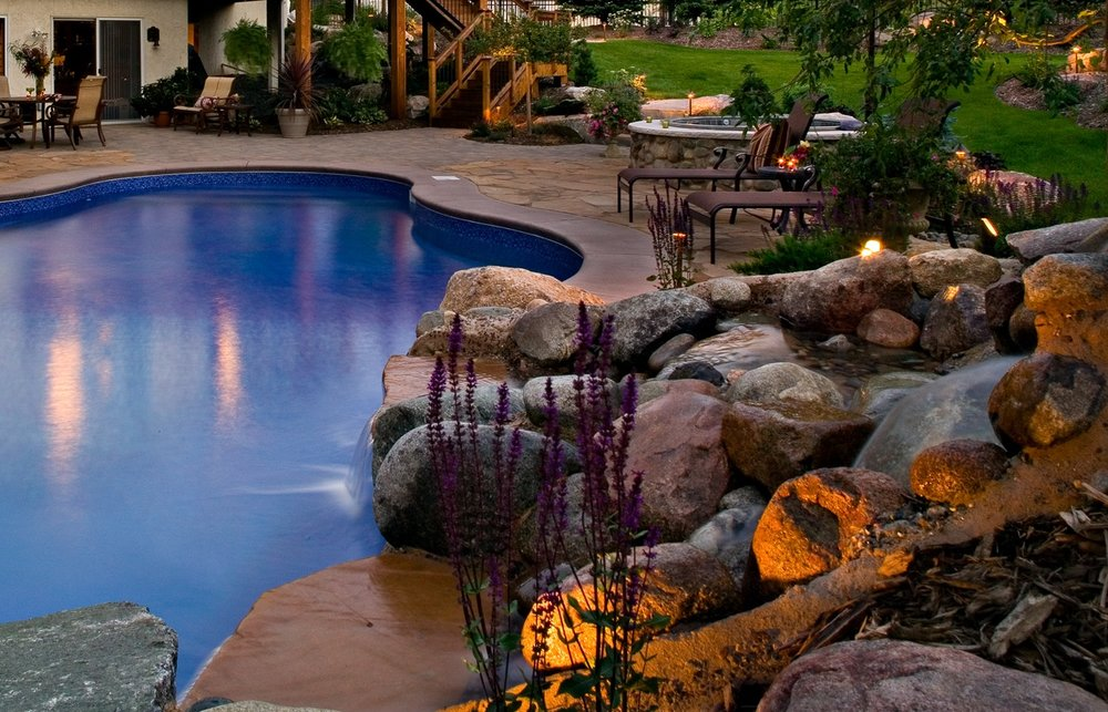This is not your average pool. A gorgeous- natural in view-  waterfall steals the show in this Eden Prairie backyard.