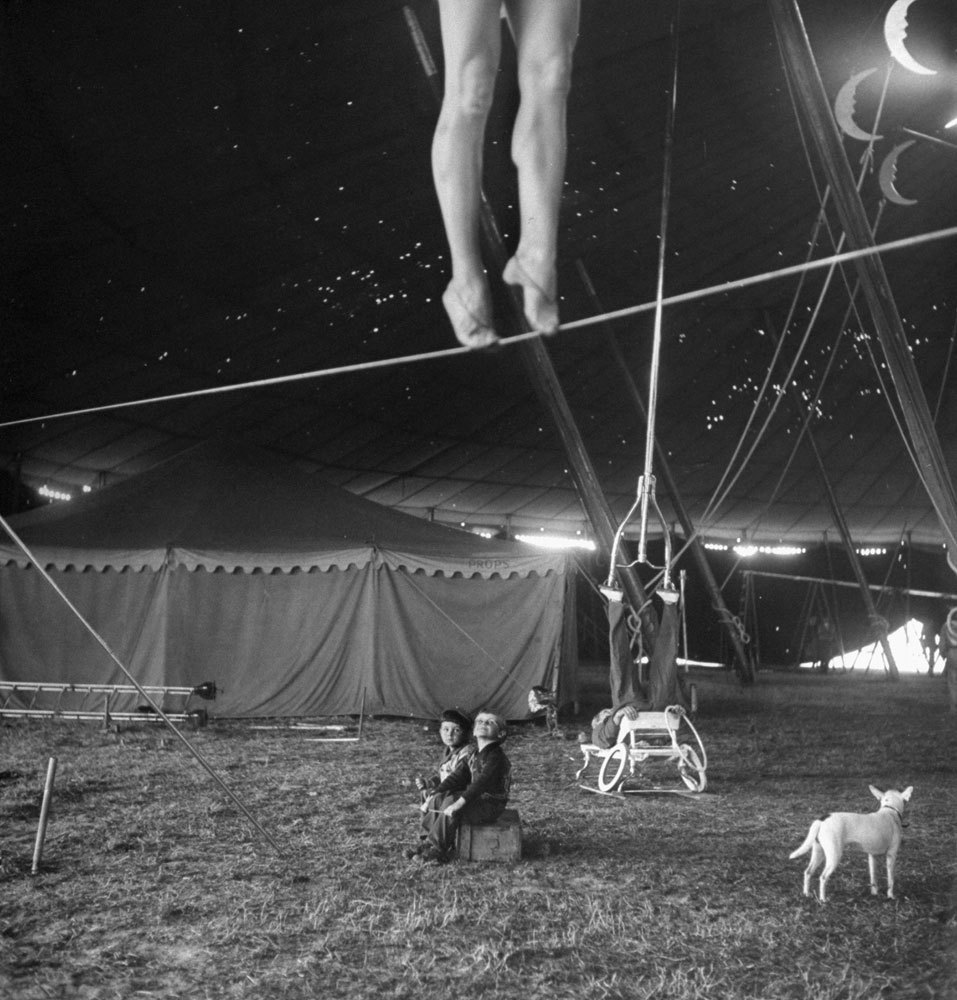 """life :       From a story on the Ringling Bros. Circus in the April 4, 1949, issue of LIFE.  The caption for this picture: """"Nothing but circus all day every day is the happy fate of these two performers' tots, who sit around the big tent watching as the pretty Miss Lola practices on a tightwire and an acrobat balances an odd contraption on his feet.""""  See more photos by Nina Leen   here.    (Nina Leen—Time & Life Pictures/Getty Images)"""