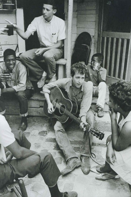 sincerelyedie :      updownsmilefrown :     Bob Dylan plays on the back of the SNCC office in Greenwood, Mississippi, 1963     One of my favorite photos ever.