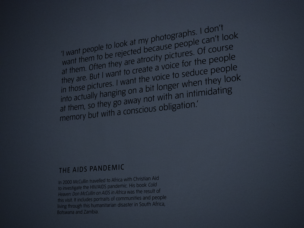 Image is of a quote by McCullin which reads: ' I want people to look at my photographs. I don't want them to be rejected because people can't look at them. Often they are atrocity pictures. Of course they are. But I want to create a voice for the people in those pictures. I want the voice to seduce people into actually hanging on a bit longer when they look at them, so they go away not with an intimidating memory but with a conscious obligation.'