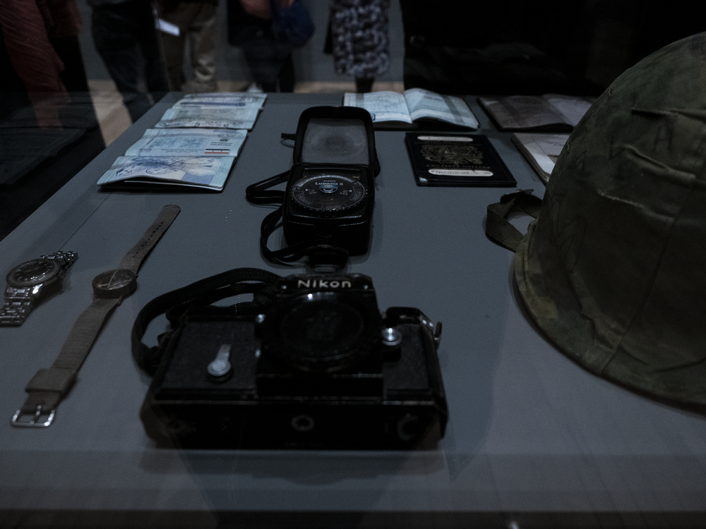 Image features the Nikon F (bullet hole cannot be seen in image but is to the left just above the lens, which is hiding it in this image), a watch, a compass, passports, work visas, light meter and helmet.