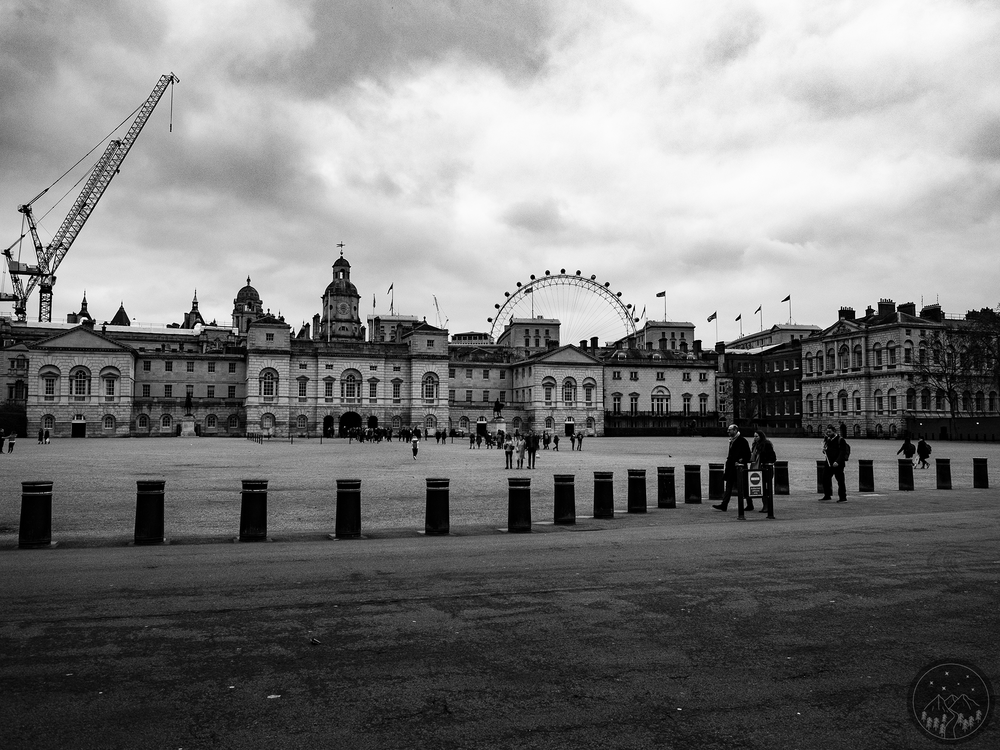 Image Description: Landscape view of Horse Guards Parade. Pedestrians are walking the street across the landscape and towards Horse Guards Parade. Cranes can be seen behind the buildings to the very far left of the image. Just past the center of the image the London Eye can be also be seen behind all of the buildings. Roughly 8+ flags are scattered over various buildings in the photo.