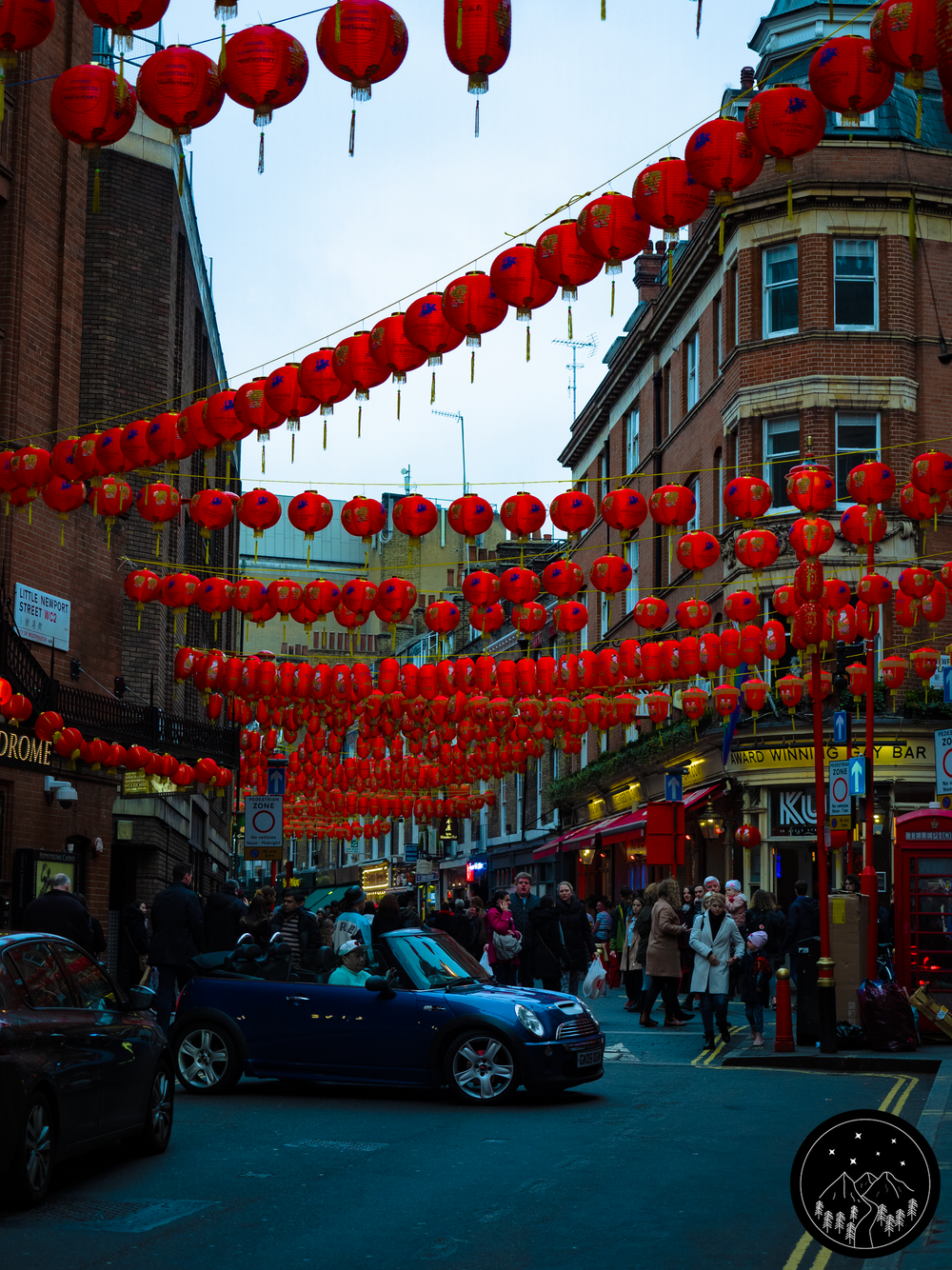 Image Description: Street photograph filled with people and buildings. From the buildings hang red China lanterns all the way up and down the street. There are also some cars in the street in front of the crowd of people which spans very far back.