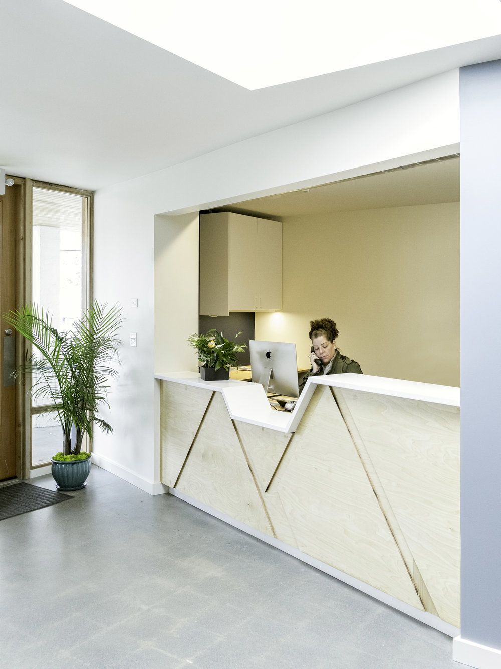 The reception desk provides a lower height section for kids to engage with the staff and the plywood facing picks up details from the Clinic logo.