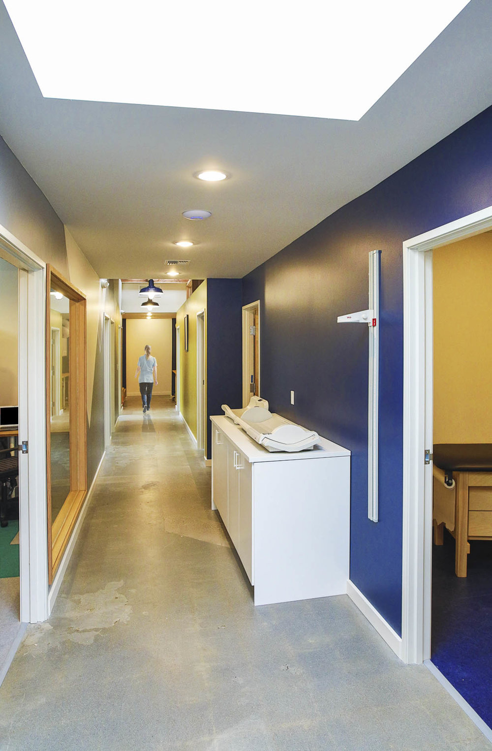 The central corridor widens where functions like charting or the weighing and measuring station occur. Interior glazing provides visual connections with the doctor and staff offices.