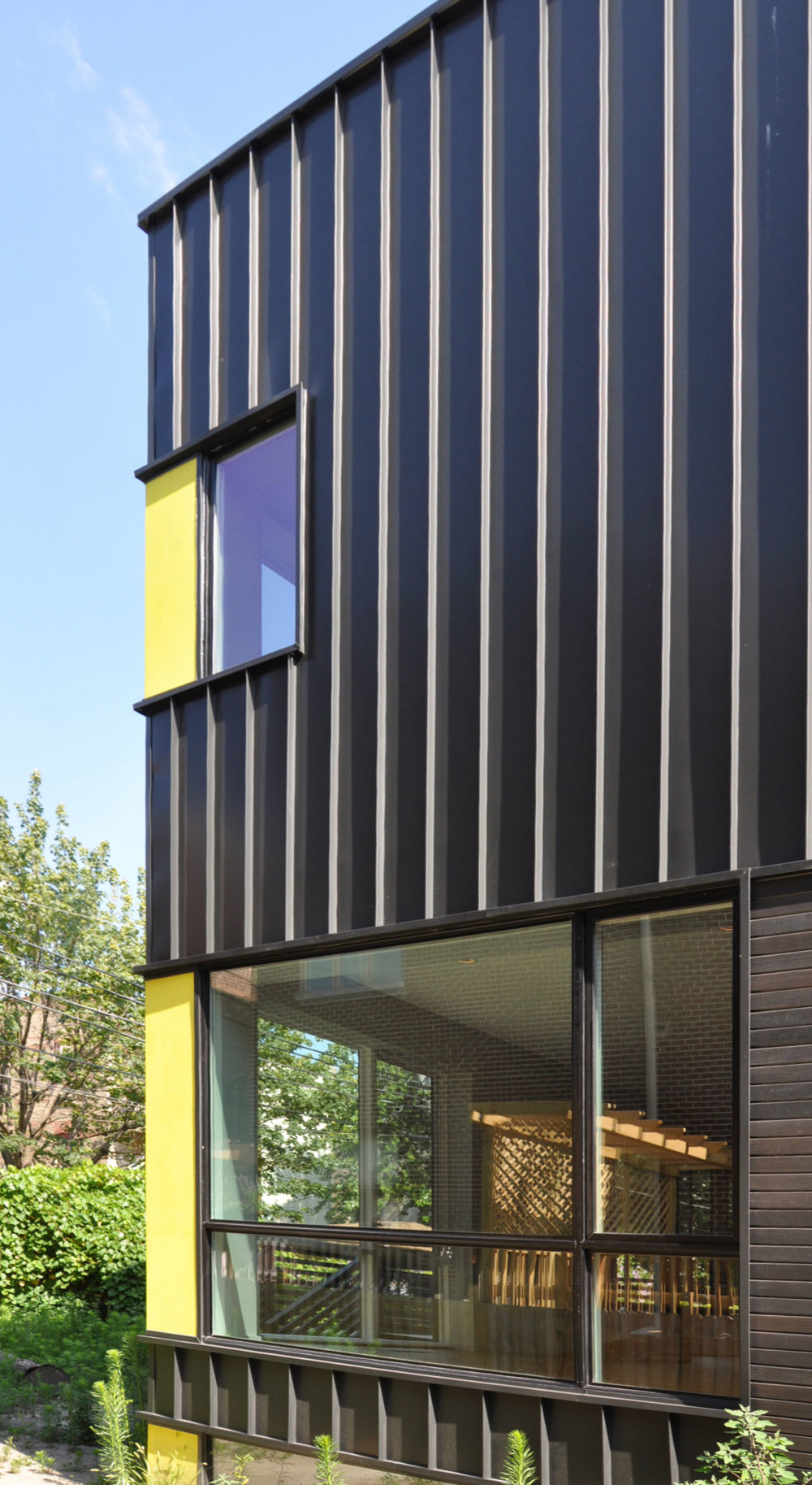 Bright yellow corner panels add color to the black standing seam metal siding
