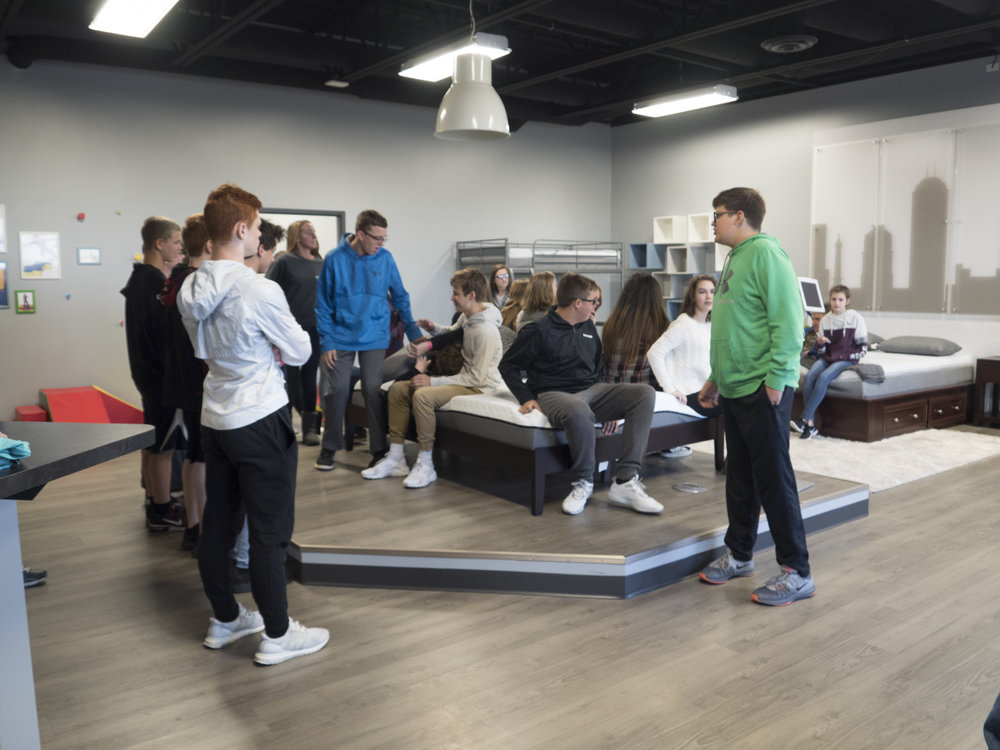 Students gather around the Mattress Customization area of the Comfort Option showroom.