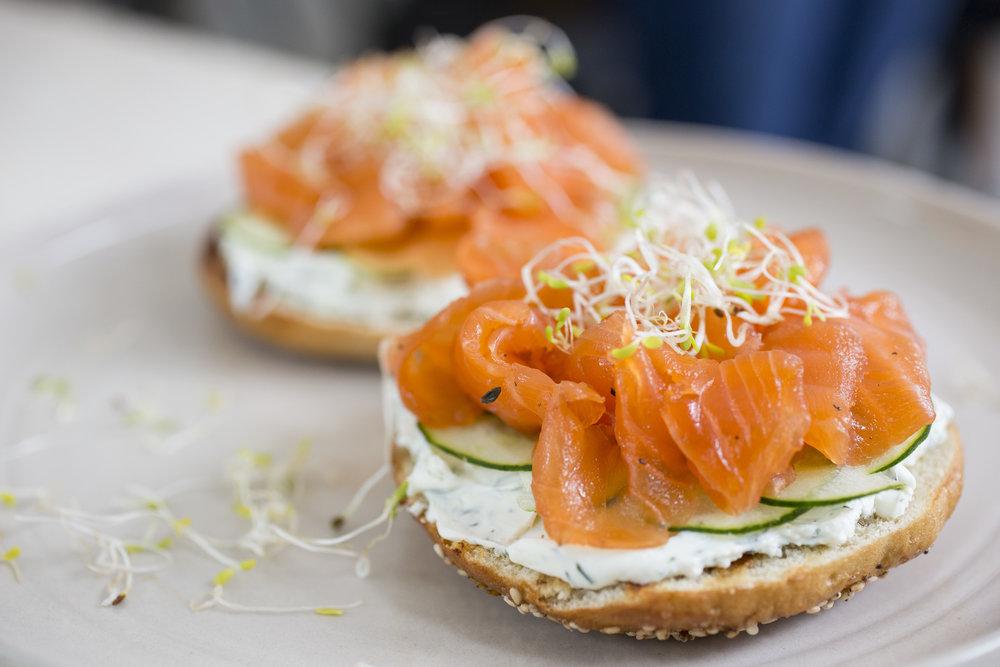 HUEVOS BENEDICTINOS:  bagel hecho en casa, queso crema, pepino, salmón.