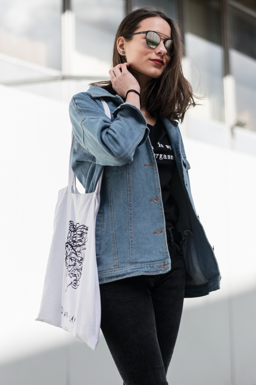 Oversized denim jacket with a pair of converse sneakers a cool tote bag and silver sunglasses, outfit by a fashion blogger fashnfudge.