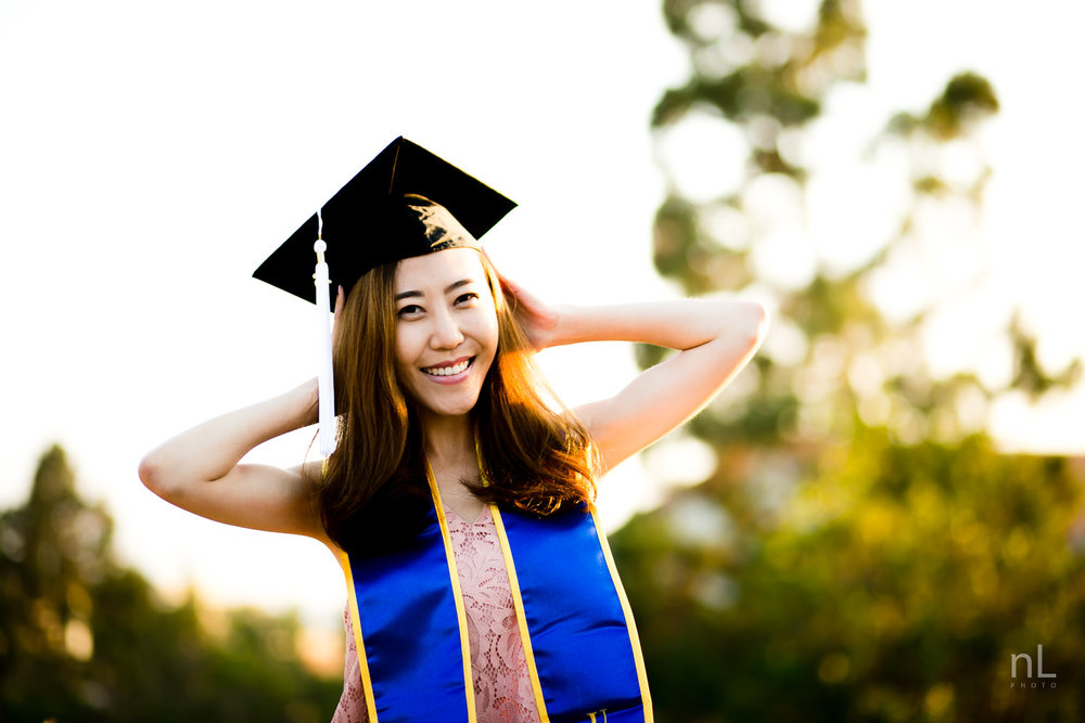 los angeles ucla senior graduation portrait asian girl in pink dress fixing cap and laughing
