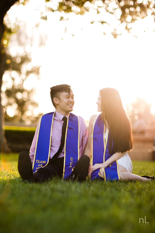 los-angeles-ucla-senior-graduation-portraits-couple-with-sashes-sitting-in-grass-sunset