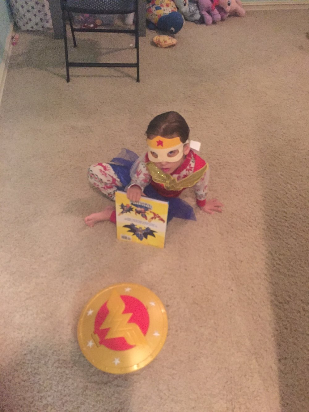 Maia put her wonder woman costume on top of her pajamas every night for months =)  She also likes to wear her mask, and the headband that came with the costume.  And her book matches too =)