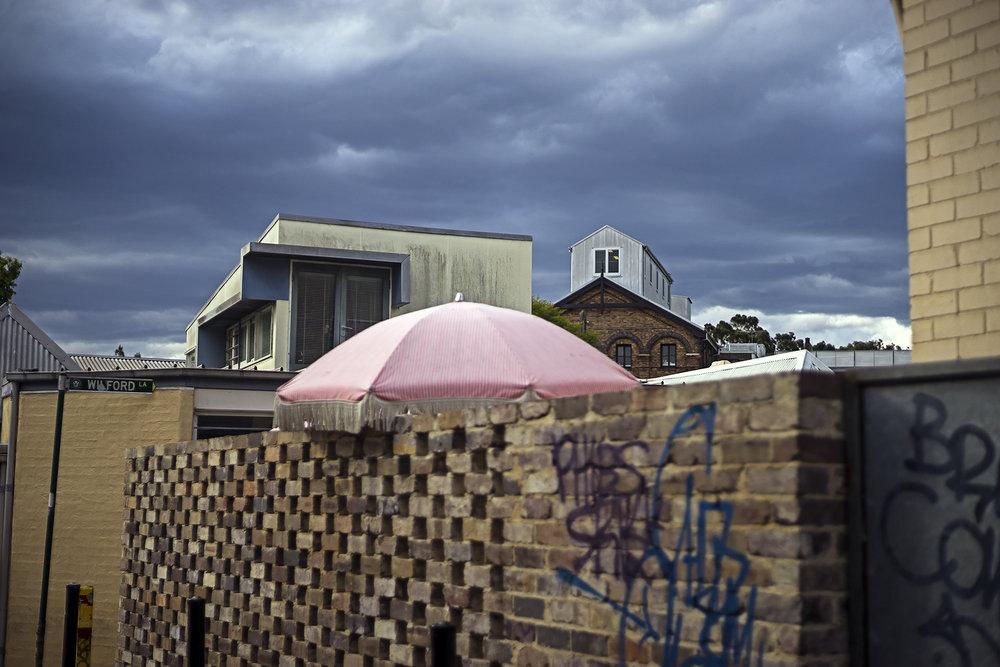 008_didi-_gilson_australian_street_photography_umbrella_newtown_sydney_storm_sky_roofs_grafitti_2018.jpg