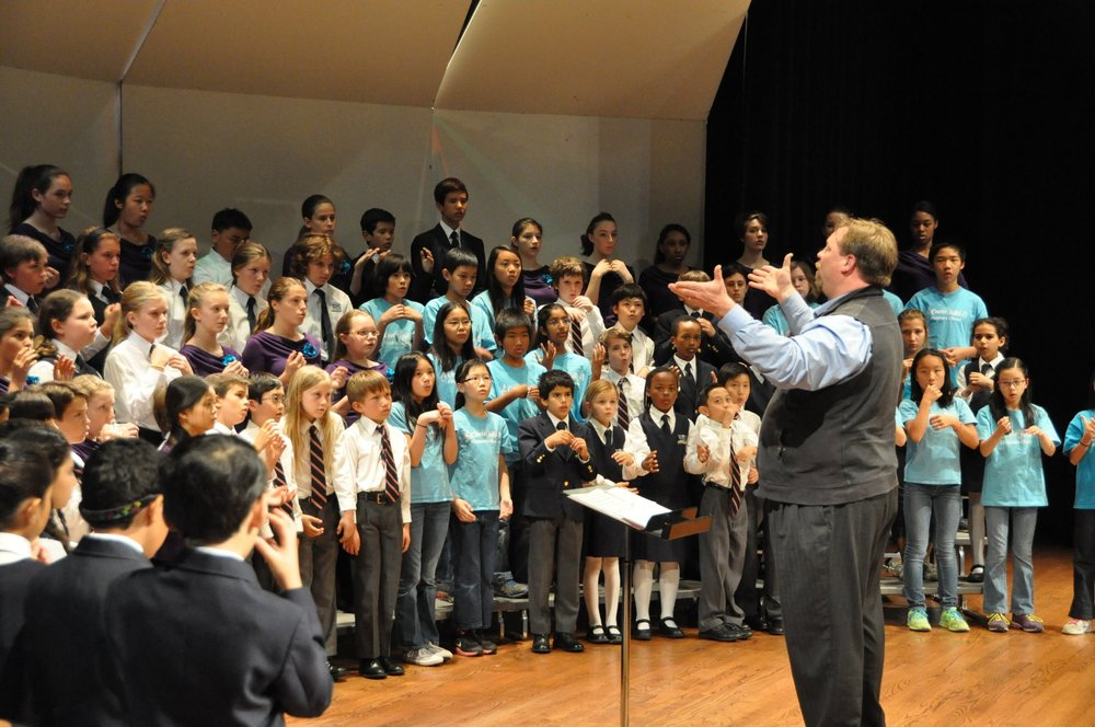 Andrew Brown    leading participants in warm-up activities for the morning session of the 2015 Children's Choral Festival at Holy Names University.