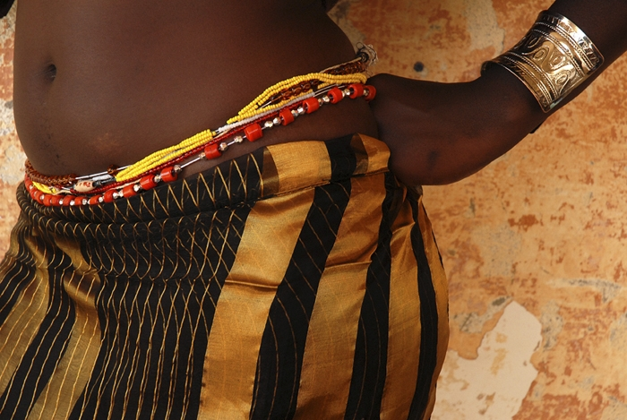 Historians note the  African tradition of waist beads  as originating among the Yoruba tribes, now mainly in Nigeria. Waist beads are also seen in West Africa, particularly Ghana, where beads signify wealth and nobility, as well as femininity. Beads were highly valuable in traditional African societies and remain so today. Beads are used for different purposes. Many African societies use beads for artwork; beads are also used for beautification. In addition to fashion, some older African cultures used various types of beads, notably glass beads, as currencies for exchange of goods and services.  Beads can serve as a means of identity. In some African communities for example, men of high status wear special kinds of beads to indicate their positions in the society. Beads can also be worn to indicate tribes or families. Beads believed to be more than 12,000 years old were discovered in Kenya, Sudan, and Libya. These beads made from (ostrich?) eggshells were used by the Turkana people as currencies that were given to women before their actual marriage as part of their dowry.  Waist beads are also found in other cultures around the world. While African and Islamic women commonly wear them under fabric, women such as belly dancers in Eastern cultures, display waist beads over clothing or against bare midsections. Some cultures believe that waist beads aid in pregnancy and encompass Earth energies. Other women, including us at Essensuals, believe that waist beads are conveyors of positive energy and healing.  Traditional West African waist beads are typically tied onto the body and worn at all times, even while bathing or sleeping. The traditional waist beads are made from various materials, including glass, wood, and metal. Traditional waist beads symbolize sensuality, fertility, and rites of passage passed down from mother to daughter. Some women wear waist beads strictly for fashion; jewels around the softest, most vulnerable part of the body can be viewed as sexy, tit