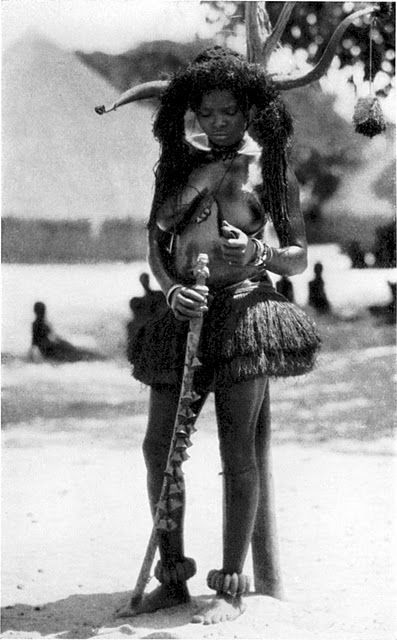 Bidjogo woman of Guinea-Bissau, with long plaited extensions, and lyre-shaped cow horns for a headdress, much like ancient Egyptian deity Hathor.
