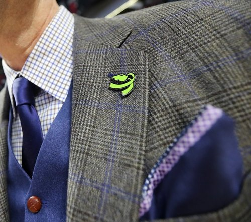 A close up of the Coaching for Literacy lapel pin, a symbol to be shown in nearly 30 Fight for Literacy Games this season.