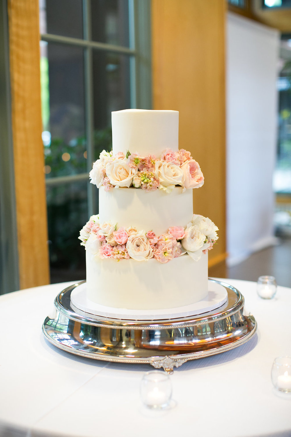 White cake decorated with flowers by Simply Cakes NC