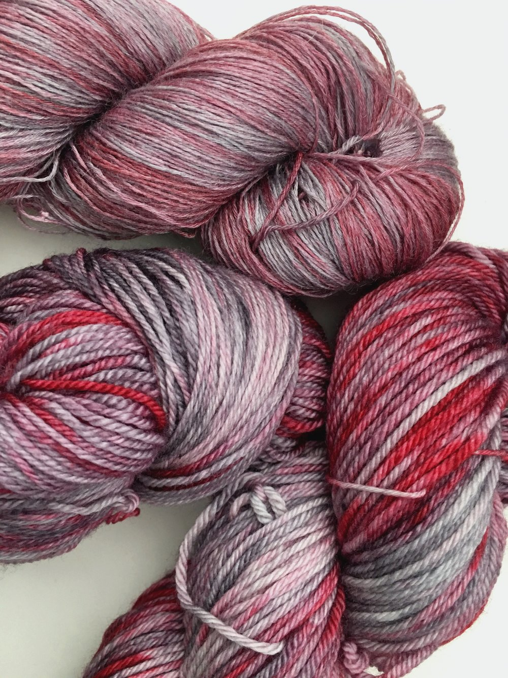 Crimson Smoke Mid-grey with rich red. Note: this color reads more pink on Aura Lace. Pictured on Aura Lace, All Your Base, and Superwash Merino Worsted