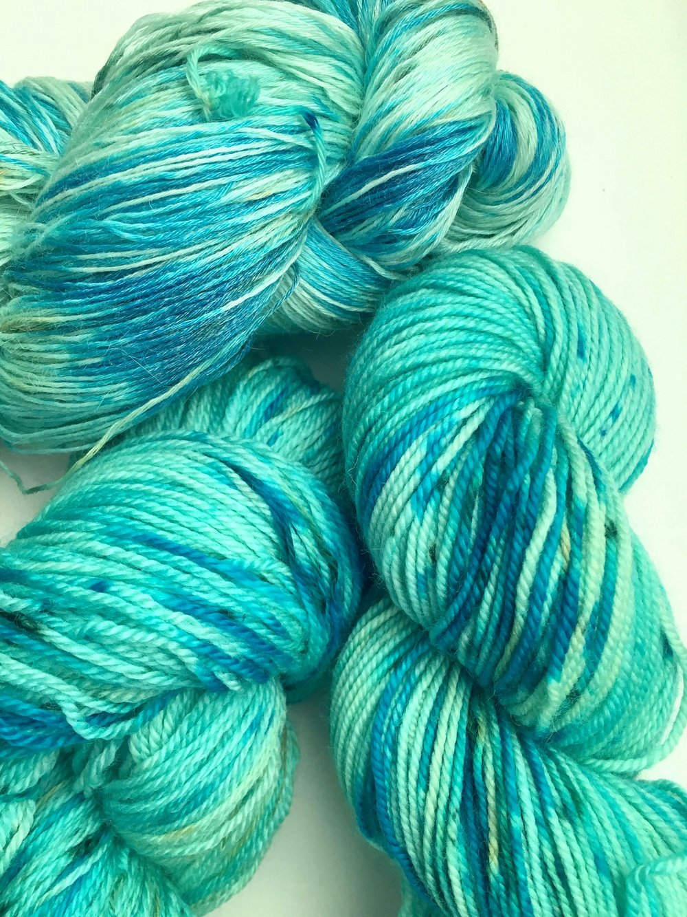 Turquoise Aqua blues with brighter turquoise highlights and green speckles. Pictured on Aura Lace, All Your Base, and Merino Sport