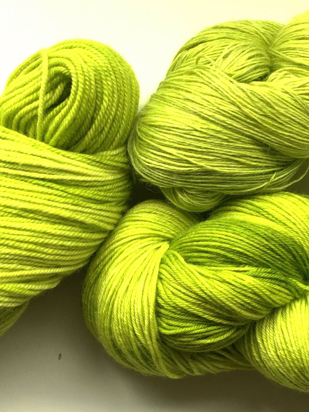 Acid Pop  Super bright, acid green. Pictured on Aura Lace, Sheepy Feet, and Merino Sport.