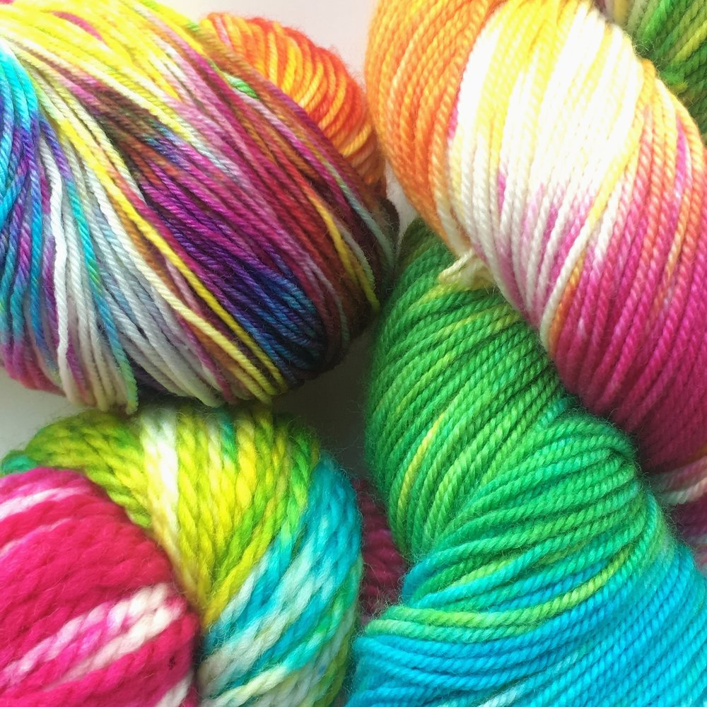 Taste the Rainbow  Bright rainbow colors from fuchsia, orange, bright yellow, lime green, teal, and purple. Shown on Sheepy Feet, Silky Merino Sport, and BFL Aran.