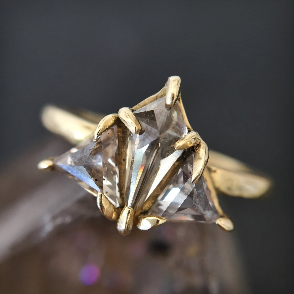 puzzle piece - A feat of congruency, just like you and yours! A .44 carat kite shaped, champagne center diamond is tucked between two champagne diamond trillions for sparkle magic.