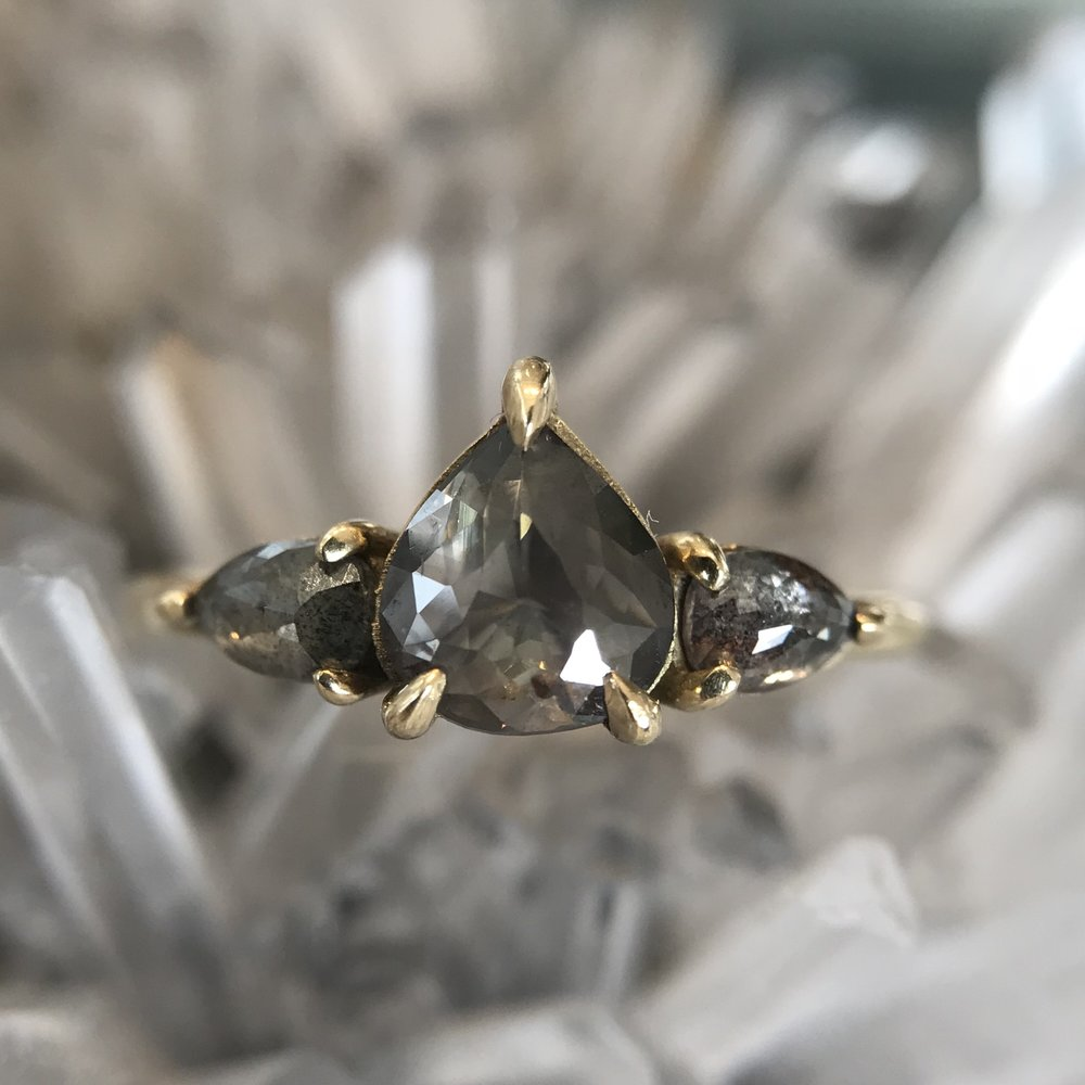 THE POWER OF THREE - Three is a magical number symbolizing the past, present & future. This three stone marvel bestows a triad of gray pear-shaped diamonds on its wearer – emblematic of lifelong love.