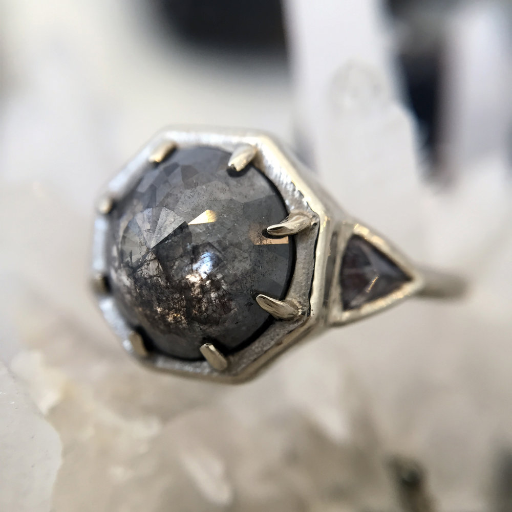 GORGEOUS GRAYSCALE - Sparkling like a meteorite flung from the heavens, this three stone wonder features a colossal 2.64ct dark gray center diamond joined by two glittering diamond trillion sides.