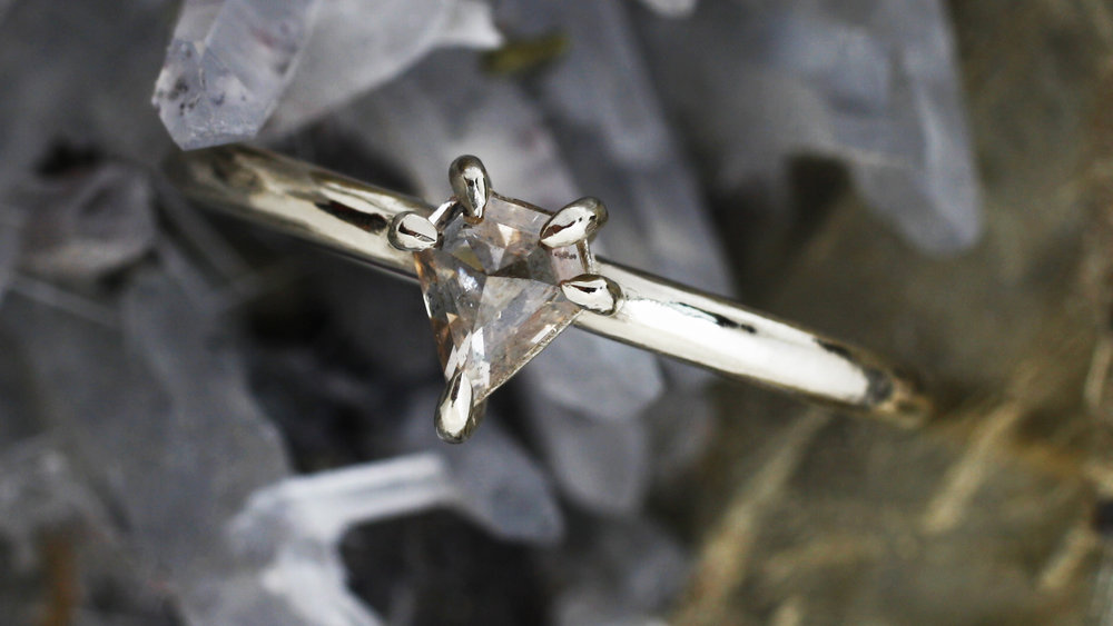 super WOMAN - A pentagonal champagne diamond sits proudly on its 18k white gold mantle. The diamond channels the super-strength of the Amazonian princess, and is stronger than any substance on Earth. Like a kryptonian star, this simple, modern ring packs a superhuman punch.