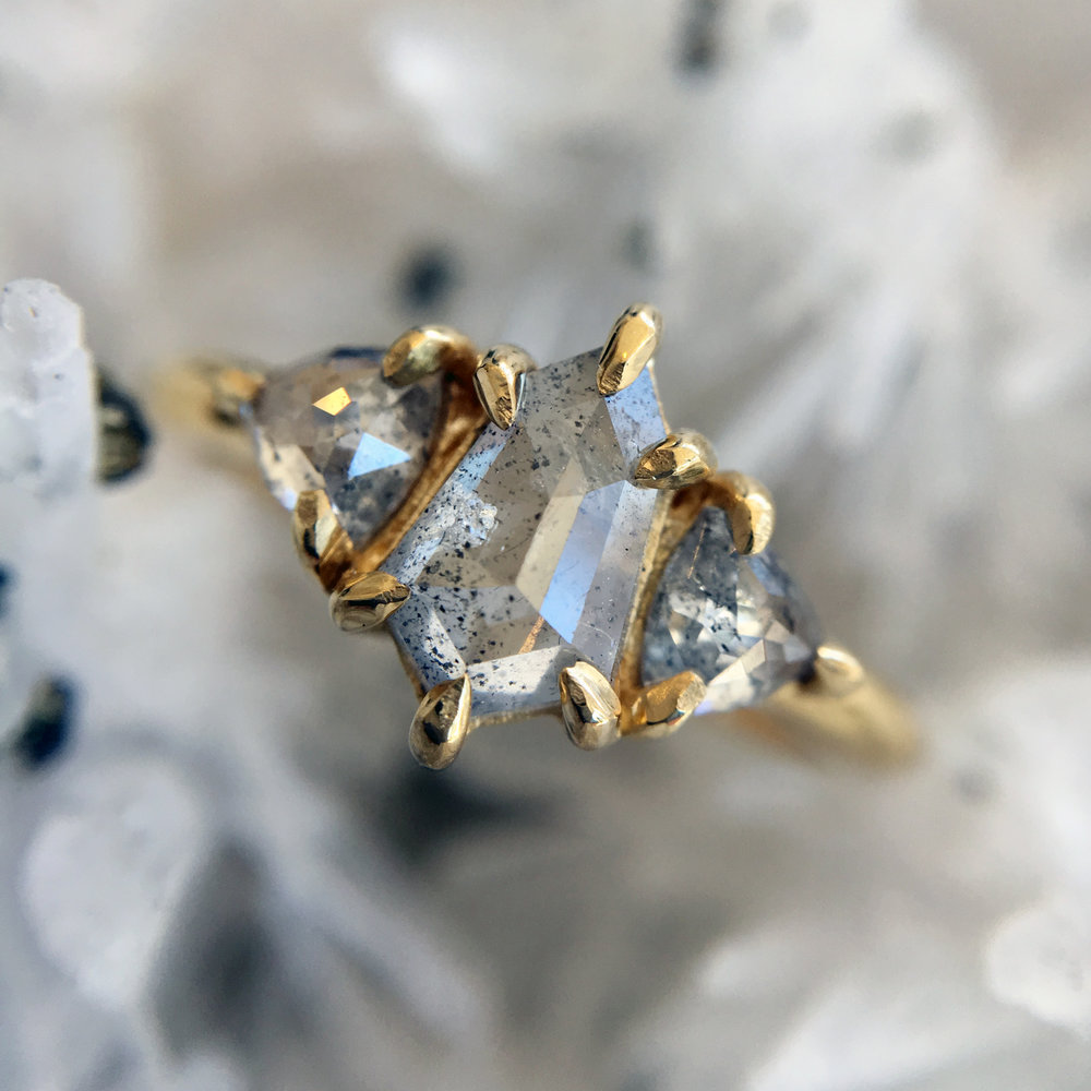 SHOT THROUGH THE HEART - A speeding bullet-cut center diamond is the rockstar in this trio of diamonds set in glorious gold. Two trillion shaped salt and pepper sidekicks sing backup while a salty gray center stone serenades the love of your life.