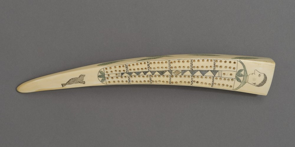 Iñupiaq, ivory cribbage board: paired holes with a human head, green leaves, and a seal; reverse: scene of a man with a whip with two dogs, a caribou, and a hunter aiming a bow and arrow at a brown bear and two seals; collected 1905. Walrus ivory engraved with black, red, and green pigment, 13 3/4 × 1 15/16 × 1 3/16 in. Hood Museum of Art, Dartmouth College: Bequest of Frank C. and Clara G. Churchill; 46.17.9690.