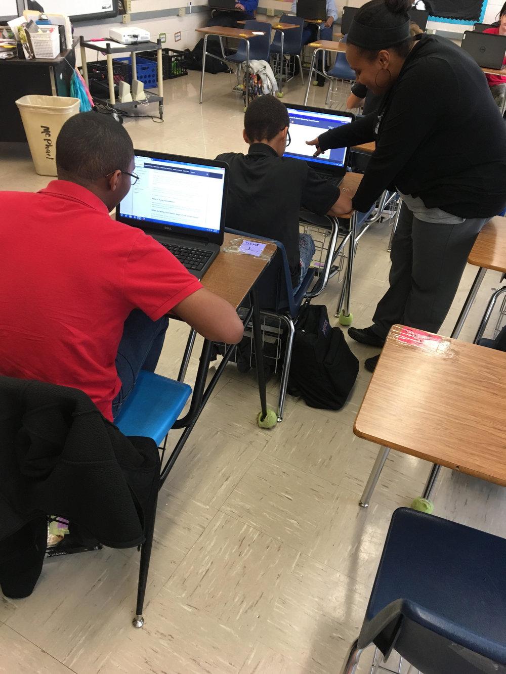 Melishia Brooks leans over to help a student.