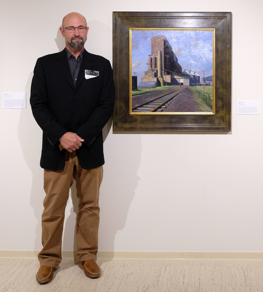 """The plaque adjoining Jeffrey T. Larson's painting reads, """"There is a rugged, majestic and honest beauty to these elevators, piers and warehouses."""" Photo courtesy of Sharon Mollerus."""
