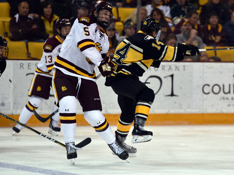 UMD defenseman Nick Wolfe avoids contact with a Tech player