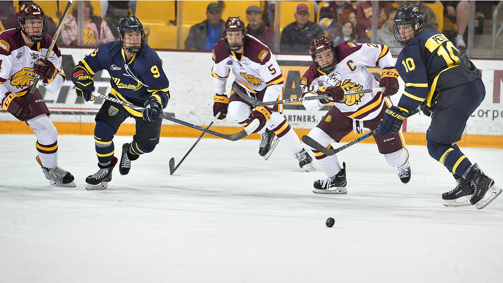 Senior captain Karson Kuhlman races for to beat a Merrimack defender for a loose puck
